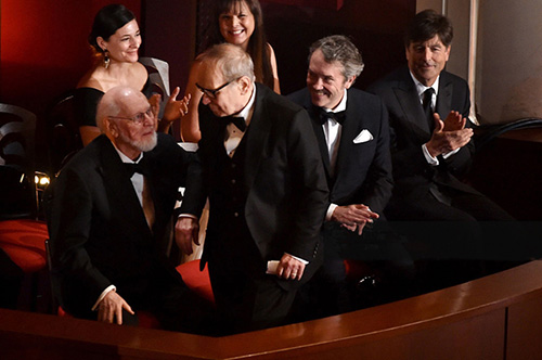 (Left to right) John Williams reaches to embrace Ennio Morricone as Carter Burwell and Thomas Newman look on.