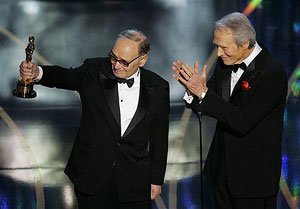 Morricone salutes his wife with presenter Clint Eastwood
