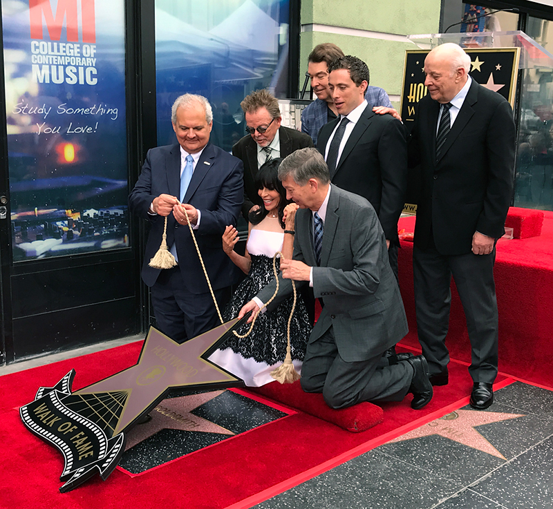 Jerry Goldsmith's star on the Hollywood Walk of Fame revealed. Standing L to R: Lyricist Paul Williams, composer David Newman, Aaron Goldsmith, composer Charles Fox. Kneeling L to R: Hollywood Chamber of Commerce Chair of the Board Jeff Zarrinnam, Carol Goldsmith, Hollywood Chamber of Commerce President and CEO Leron Gubler.
